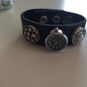 """Læderarmbånf med udskiftelige """"trykknapper"""". Der følger også et ur med. Brugt 1 gang"""