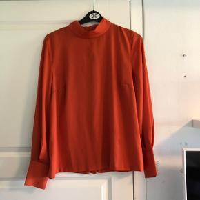 Orange bluse fra H&M med knapper langs ryggen. En størrelse 44. Fremstår som ny