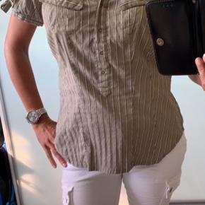 Grå med sølvstriber og bindebånd ved ærmerne.. Lækker skjorte med en go pasform.. Der står godt nok str. XL i skjorten med den svare altså til en S/M Brystmål - 2x 49 cm. Længde - 62 cm. Materiale ses på sidste billede.. Befinder sig i Tarup Odense NV