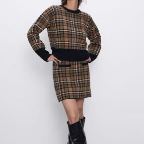 Det fineste miniskirt i en form for strik og tern.   Aldrig brugt og med prismærke.   Perfekt til efterår!