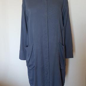 Stor i str. - vil også kunne passe M. Fin kjortekjole. Denim lignende. Flot fald. Skjult knaplukning ned foran og har kommer. Kun brugt et par gange. Længde ca 90 cm. Lavet i lyocell.