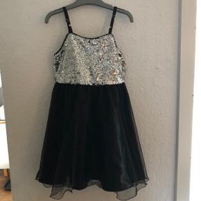 Flot kjole med palietter i str 128 af mærket jocko.Kan bindes med sløjfe bag på med bindebåndet. Se billede 2.   Har været brugt som nytårskjole og kjolen til fester.   Giv et bud  Befinder sig i Mejls ved Varde