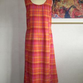 Sød ternet bomuldskjole i farverne røde-orange-gule farver. Knapper ned foran og lommer i sidesømmen.   Brystvidde: 55 cm x 2 Livvidde: 50 cm x 2 Længde: 131 cm  Ingen byt og prisen er fast