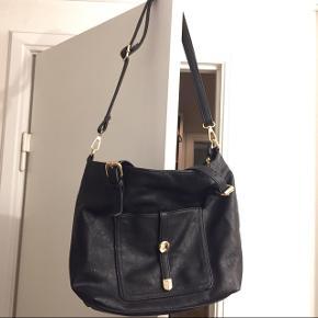 Sort taske med guldfarvede detaljer. Korte håndtag og skulderrem, så den kan bruges til lidt af hvert. Mange dejlige rum!  Kan afhentes eller sendes!
