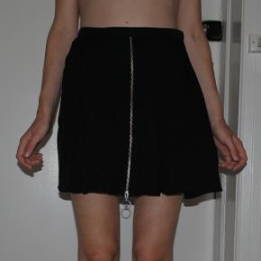 Nederdel med fuldt skørt og lynlåsdetalje foran (nederdelen lukkes med usynlig lynlås i siden).