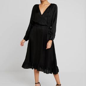 Ualmindelig smuk kjole med bindebånd i begge sider. 100 % viscose der falder tungt, blankt og utrolig lækkert. SMUK til strømper, smuk med læderleggins under, men må bare erkende, at jeg ikke er en kjolepige, og så må den videre. Nypris 1545, sælges til 600, som er LANGT UNDER HALV PRIS,. Kan ikke huske str. da jeg har klippet den ud men den vil passe både en L og en XL da den kan løsnes og strammes ind i taljen. Der er plads til stor barm, så den er også der det største til mig. Masser af smukke detaljer. Flæse forneden, og flæsekant ved ærmerne.