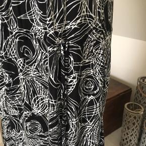 Kjolen kan snøres i livet, eller man kan lade den hænge løst.  Længde fra skulder og ned: 103 cm.