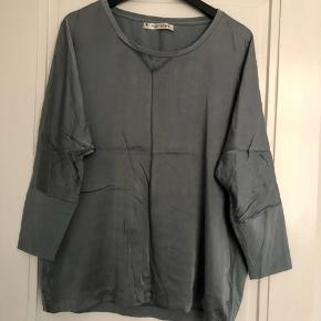 Fineste bluse med silke foran og ryg i bomuld. Flot støvet turkis/petroleum.  Brystbredde ca. 61 cm.  Længde ca. 67 cm.  Bytter ikke!