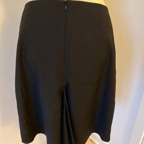 Smuk fin og ny nederdel med fin detalje bagpå og 2 strå lommer foran