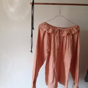 Vintage støvet rosa (lyserød) skjorte med flæser i dansk design. Er oversize selvom set ikke rigtig kan ses på billedet :) er en str 36, men kan nemt passe en str 38 og stadig være oversize. kan strammes ind i ærmerne.