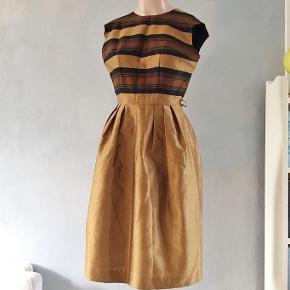 Gylden, let bronzefarvet kjole fra ca 1960🐱  Så fin🧡💛🧡 Det er en str S. Terylene og uld i satinvævning. Kjolen er foret og har lynlås bagpå. Bryst 93cm. Liv 63cm. Hofte 130cm.  Se også mine mange andre sager. Jeg giver gerne mængderabat  . #60erkjole #50erkjole #vintage