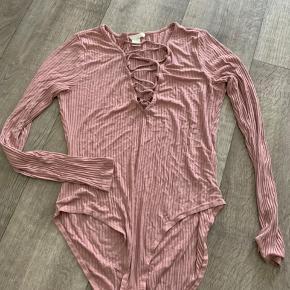 Fin ribbed lyserød/rosa bodystocking fra H&M. Den har nogle snore foran som man kan justere ved at hive i siderne eller snorene. Max. brugt 1 gang og det har ikke været uden en underdel under.  Str. M Byd gerne selv :)