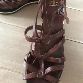 Varetype: Sandaler Farve: Brun Prisen angivet er inklusiv forsendelse.  Flot remsandal med 10 cm høj hæl bagtil, 2,5 foran. Ikke brugt ret meget.