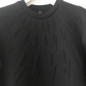 """Helt ny og ubrugt, stadig med mærker sort sweatshirt fra tjekkede britiske Neil Barrett. Den er købt til et runway show i Paris og kostede 4.799kr. De fede og meget ikoniske """"lyn"""" som Neil Barrett er kendt for at have som varemærke blandt andet, er i en 3D effekt på sweatshirten. Lavet i Italien."""