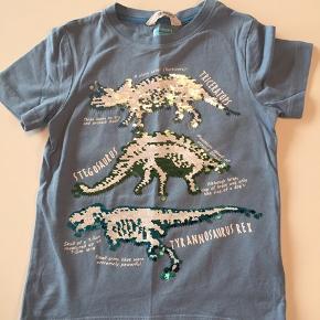 Dinosaur t-shift str. 110/116 (dog lille i str.). Kun brugt et par gange. Palietterne kan vendes.