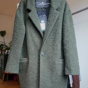Blød mørkegrøn / army grøn frakke fra Designers Remix i str. 38. Nypris 2800. Jakken er aldrig brugt og har stadig prismærke på. Frakken har en løs pasform, to stik lommer foran og er super dejlig at bære.  Gå efteråret i møde i denne smukke uld frakke. Løs pasform.   Shell: 60% wool, 40% polyester. Lining: 100% cotton