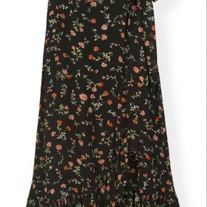 PRINTED GEORGETTE WRAP SKIRT SORT GANNI Sort højtaljet slå-om-nederdel med blomsterprint, bindebånd i taljen og flæsedetaljer. Har kun været prøvet på og aldrig brugt.  Køber betaler Porto
