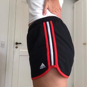 Sorte løbeshorts med orange detaljer fra Adidas.