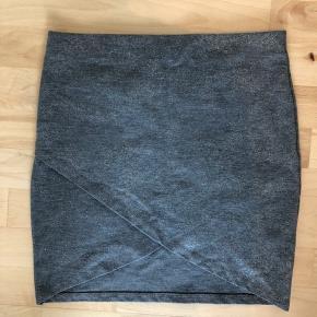 Nederdel i grå/sølv - str. M. Flot slå-om-detalje foran. Aldrig brugt.   Afhentes i Aalborg eller sendes mod betaling af porto