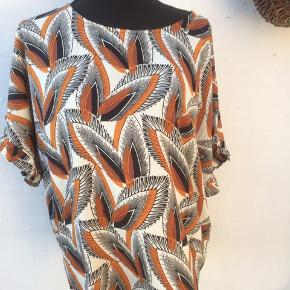 Bluse i sort, råhvid og rust Brystmålet er 2 x 70 cm Længde 70 cm Polyester