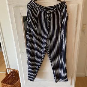 Løse bukser med bindebånd i taljen fra Monki. De har blå og hvide striber. Kun brugt én gang, da de er for store.
