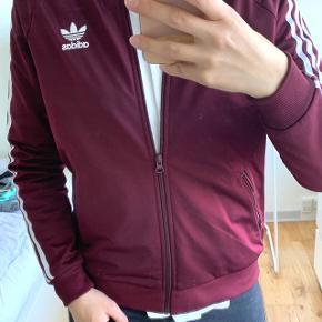Adidas sweatshirt med lynlås  Den er næsten ikke blevet brugt, hvilket fremgår meget tydeligt. Trykket bagpå samt lynlås er i fineste stand.  Mener nypris på de her sweatshirts ligger på omkring 400-500 kr  200 kr