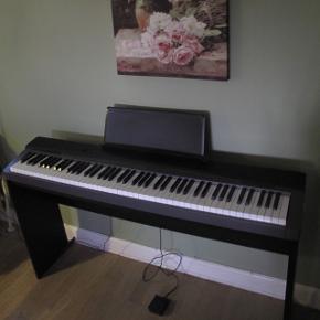 Carsio Privia PX-130, sort. Kompakt digital-piano med 128-toners polyfoni, 128 anslagsfølsomhed, 16 lyde og 8 effekter. Inklusiv pedal og stativ samt mikrofon + stativ og høretelefoner til klaveret. Klaveret alene er 5.000kr værd 😊🙌🏻