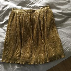 Lille i størrelsen, passer nærmere en S/M. Fin plisseret nederdel. Lukkes med lynlås.