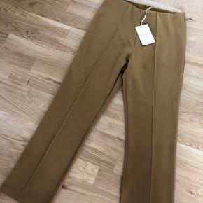 Bukserne er aldrig brugt og har stadig prismærke på. De super fede og i en mørk karry gul farve - men måtte desværre erkende, at de ville blive for små.