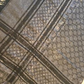 Gucci tørklæde vendbart sølv/grå på den ene side og sølv/sort på den anden side.  God men brugt da der er et lille hul og trukkede tråde. Ses ikke når man har det på.