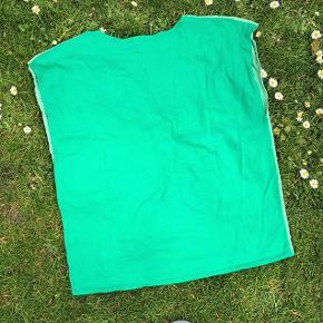 T-shirt uden ærmer i Grease-stil. Flotte kantbroderier og broderet logo.  Toppen er håndlavet, så der findes ikke en eneste, der er magen til.  Grøn str. 38, blad-applikation, forskellige grønne farver for og bag. Omkreds ca. 93 cm, højde midt bag ca. 53 cm. Materialet er bomuldsjersey.  Sælges for kun 30 kr. + evt. porto.  Kan afhentes på Frederiksberg.