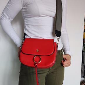 Fin rød taske i ægte læder. Næsten ikke brugt. Ingen synlige tegn på slid. Remmen kan skiftes, den grå/grønne fulgte med ved køb. Tasken måler 19x16 cm og 8 cm i bunden.