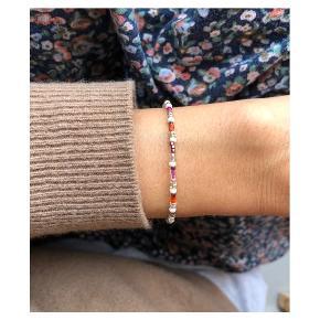 Perlearmbånd Beige, sølv, lilla, røde perler Lås: messing Mål: 16,5-17,5 cm Prisen er inkl Porto med postnord