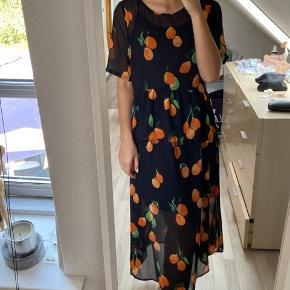 Brugt én gang. Super smuk kjole med appelsin print. Er i mesh stof, sort underkjole medfølger. Kan passes af en xs og en s
