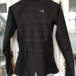 Sort og grå softshell jakke, så der er nem bevægelighed. Lækker kvalitet og nypris var 1199 kr. Aldrig brugt. Sidste billed er taget med blitz, så perfekt løbejakke også, til de mørke aftener.