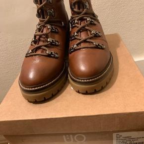 Brune / gyldenbrune skind chunky hiker boots i str 37 Normal i str - ej små (vil mene de passes af str 37-37,5) Total højde målt bagpå ca 15-15,5 cm Hæl ca 4 cm og front sål ca 2 cm Målt fra kap til snude indvendig ca 24,8-24,9 cm Model: Bow Hook Hiker Købt i 19 Har også et par i 36 & et i 39 som r hhv 1 cm mindre og større i længden for hver str. op eller ned) Hvis afhent 260 (38 r solgt)