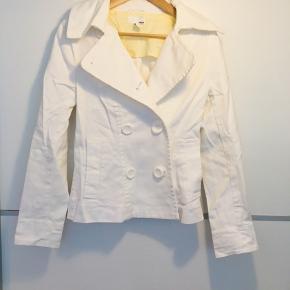 Sød jakke i trenchcoat stil. Jakken er figursyet. Den er aldrig brugt og har stadig prismærke på. Har kostet ca 225kr fra ny. Jakken er hvid med knapper