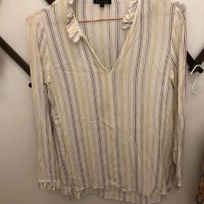 Fin hvid skjorte med gule, lilla striber og fræser på ærmer og udskæring v hals