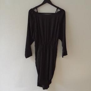 Fin, sort kjole med åben ryg med strop-detaljer, stropper ved skuldre, lommer og lille slids i begge sider. Elastik i taljen.  Er lidt mat i farven, men står stadig meget fin!
