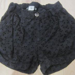 STR. 122/128. Super søde sorte shorts i broderi anglaise. Der er fastsyet foer i, således at de ikke er gennemsigtigt i broderiet. Der er justerbar elastik i livet (dog mangler knappen i den ene side), /men i vaskemærket sidder en ekstra knap, som man kan bruge..  Der er 2 sidelommer og 2 baglommer. 100% bomuld.  Porto: 37 kr. sendt som pakke uden omdeling med DAO.  Jeg har tøj til både baby, piger, drenge, kvinder og mænd i stort set alle størrelser. Send mig blot din mailadresse, og skriv hvilke størrelser du er interesseret i. Så sender jeg en mail retur med billeder/beskrivelser/priser.