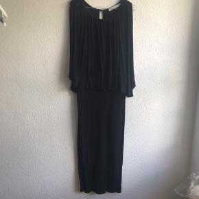Flot sort kjole i viskose med stræk. Ærmet er bart på skulderen men falder smukt og draperer ned langs siden. Lille knap i nakken