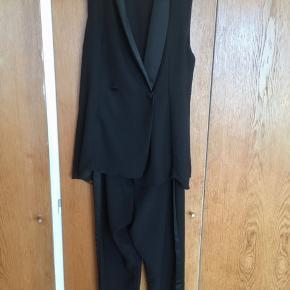 Virkelig lækker og klassisk ærmeløse blazer jumpsuit fra Zara Basic. Buksedragten består af et par klassiske tætsiddende bukser pg en virkelig flot ærmeløs blazer/tuxedo/vest. Er i ét stykker og lukkes foran.  #trendsalesfund