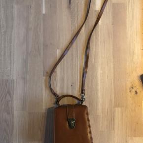 Skulpturel vintagetaske i brun læder. Kan bruges både med og uden skulderrem.
