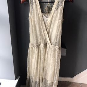 Supersmuk kjole - aldrig brugt. Uderkjolen er 100% silke og måler 90 cm fra bund og op til stropper. Selve kjolen er polyamid og viskose og måler 115 cm. fra top til bund. Jeg gav knap 600 for den (det var halv pris). Har stadig bon. Hentes i Hjørring. Kan sendes for 50kr.