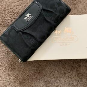 Ny pung fra Coach i original æske, møntrum med lynlås, 2 rum til sedler, samt plads til 12 kort. Pris i butikken 900kr. En stor model 10 x 20 cm.