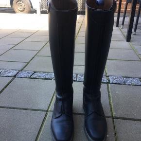 Velholdte sorte Petrie Athene ridestøvler.  Da de kun er brugt ca 3-4 måneder, skal de stadig rides til - de er kun blevet lidt bøjelige ved anklen.  Lidt mærker efter sporer bag på, ellers ingen fejl. Se billede for størrelsesforhold - jeg bruger normalt selv en størrelse 38 i foden.   De kan afhentes i Kolding (København er også en mulighed)