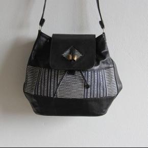 Håndlavet taske i læder og håndvævet detalje.  Lukkes med bindebånd og magnet.  Små lommer og opdeling indvendig