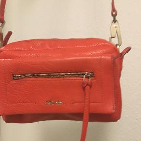 """Super flot taske fra """"Calvin Klein"""" Mål: 20 x 13 x  4 cm  Omkreds hank kan reguleres  Farve: orange  Fast pris  Bytte ikke  Sender med Dao 37kr"""