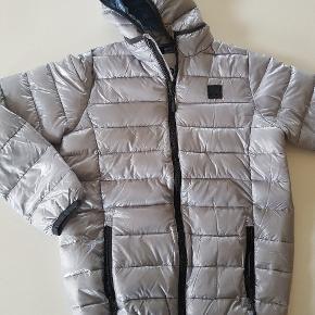 Vatteret vinterjakke i sølv. Ny. Str 164. Nypris 650 kr.   God overgangsjakke da den ikke er så tyk og dermed god når sommerjakke er for kold og vinterjakke for varm.   Køber betaler evt porto. Dao 38 kr.