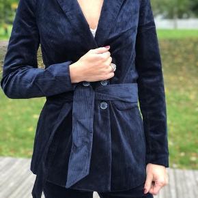 Helt ny blazer fra Munthe i mørkeblå fløjl. Modellen hedder 'VELTURE'. Kan bruges med eller uden medfølgende bælte.